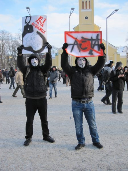 Foto: Zwei Anti-ACTA-Demonstranten mit Guy Fawkes-Masken und hochgehaltenen Transparenten