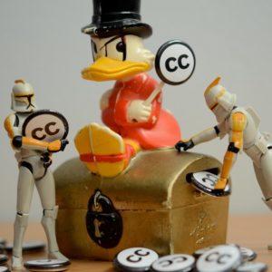Foto: Dagobert Duck-Figur auf einer Schatztruhe, in die «CC»-Münzen geworfen werden