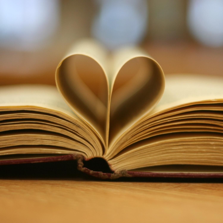 Foto: Aufgeschlagenes Buch, bei dem zwei Seiten in der Mitte ein Herz bilden