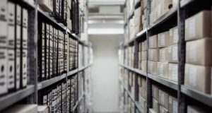 Foto: Blick in ein Archiv mit Ordnern und Schachteln auf Regalen