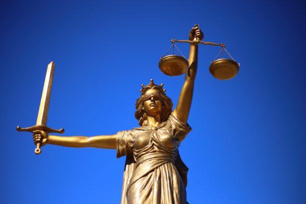 Bild: Justitia mit verbundenen Augen vor blauem Hintergrund
