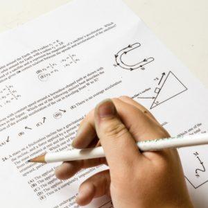 Foto: Hand mit Bleistift, die Prüfungsaufgaben löst (Symbolbild)