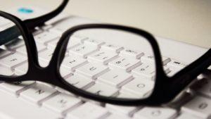 Foto: Schwarze Brille, die auf einer weissen Tastatur liegt
