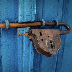 Foto: Blaue Holztüre mit rostigem Riegel