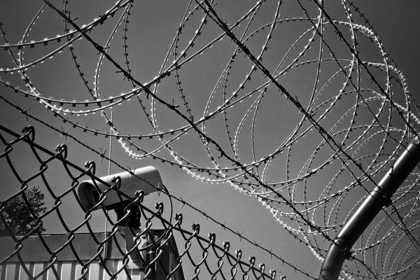 Foto: Zaun mit Stacheldraht und Überwachungskamera