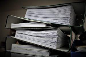 Foto: Stapel von mehreren Ordnern, die mit Papier gefüllt sind