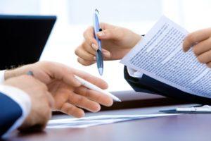 Foto: Hände mit Dokumenten und Kugelschreibern