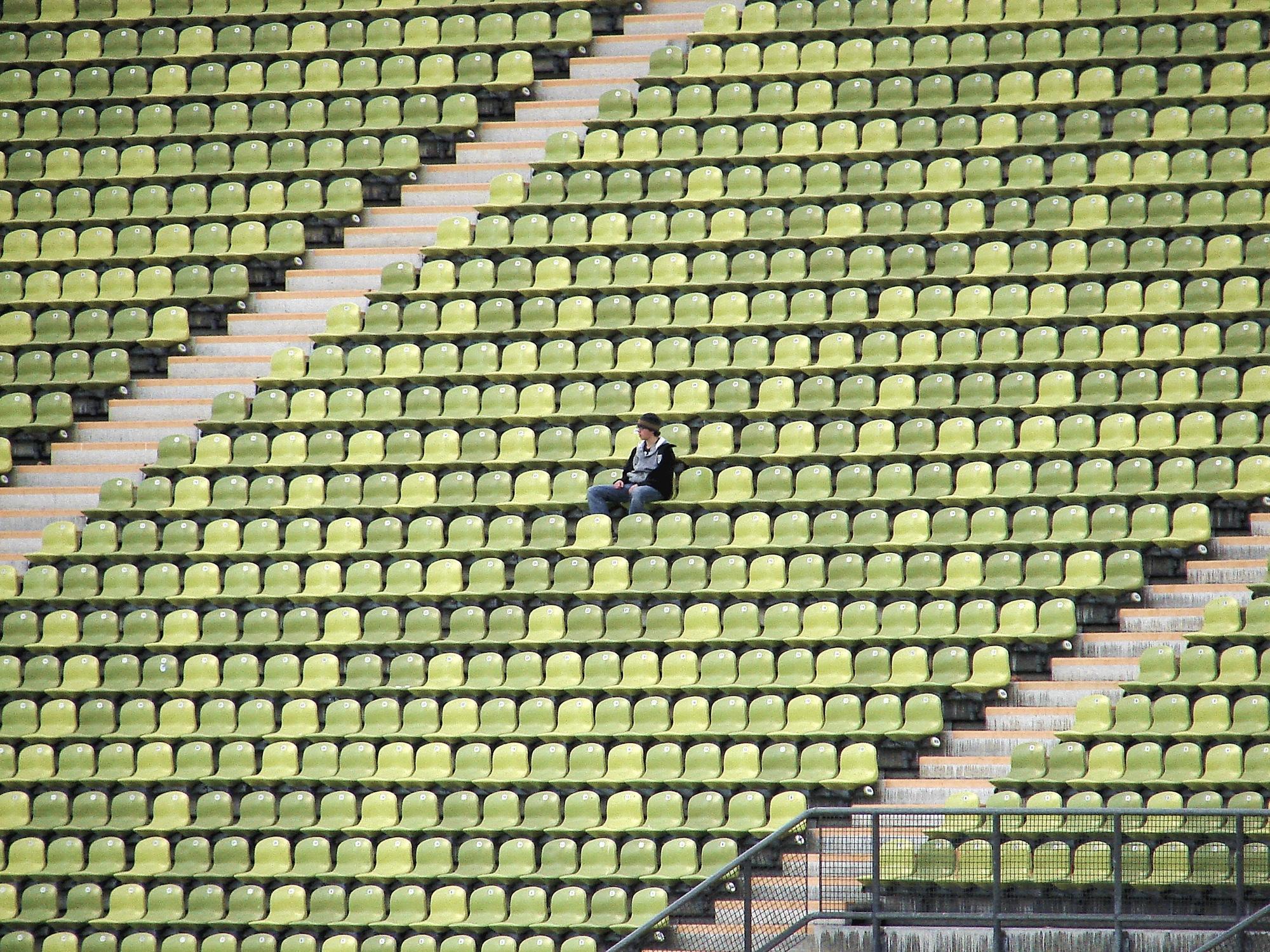 Foto: Einzelne Person sitzend auf der Tribüne in einem Stadion