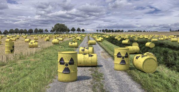 Bild: Zahlreiche Fässer mit Atommüll, die auf Feldern und Wiesen liegen (Fotomontage)