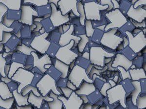 Foto: Viele ausgeschnittene Facebook-Likes (Blau-weisse Händchen aus Karton mit ausgestrecktem Daumen)