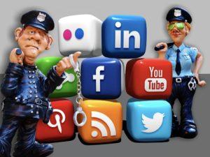 Bild: Polizei-Figuren (Polizist und Polizistin jeweils in Uniform) mit zahlreichen Würfeln, die aufgestapelt sind und die Logos von Social Media-Plattformen zeigen