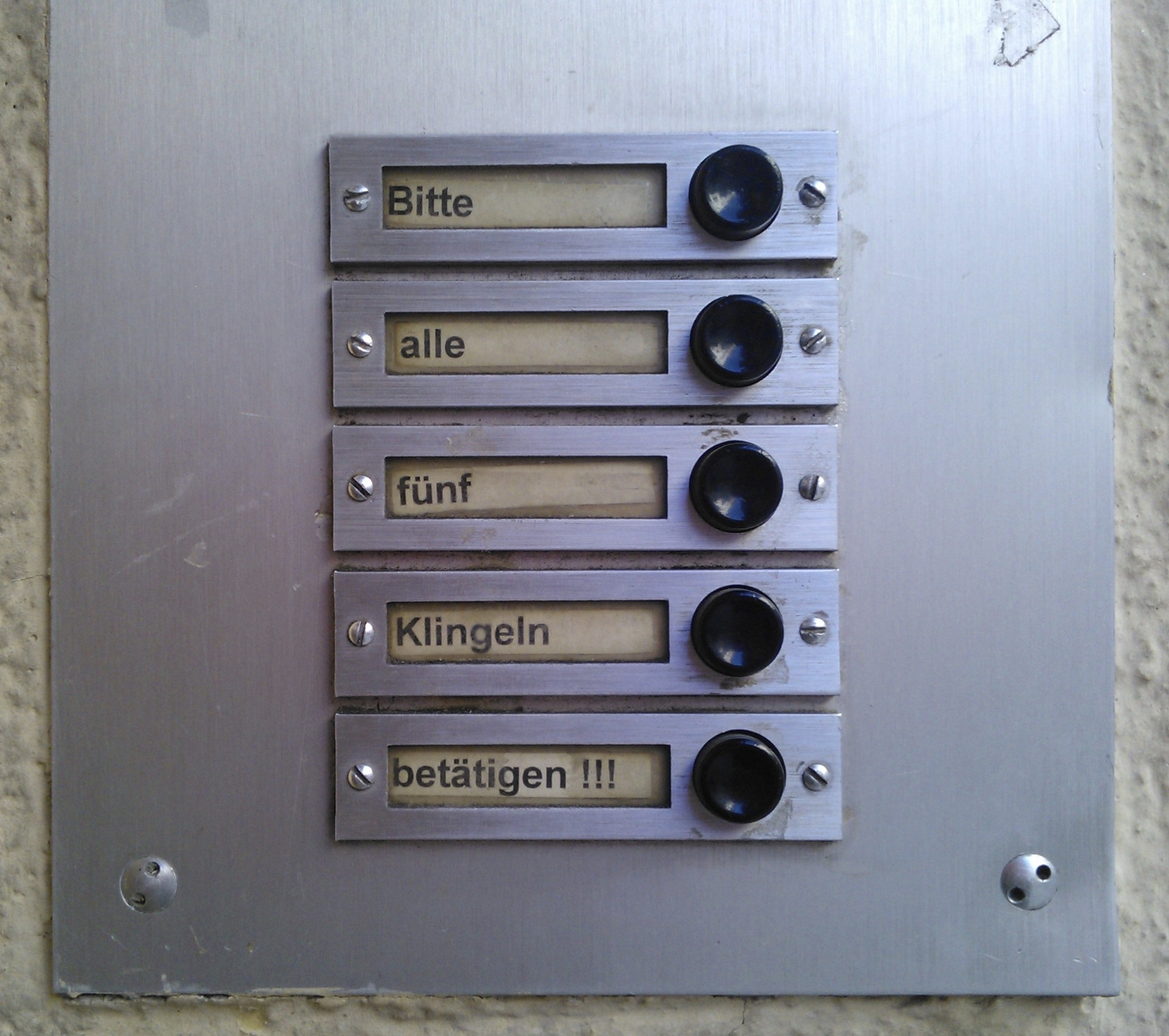 Foto: Fünf Türklingeln in vertikaler Anordnung mit der Beschriftung «Bitte» «alle» «fünf» «Klingeln» «bestätigen !!!»