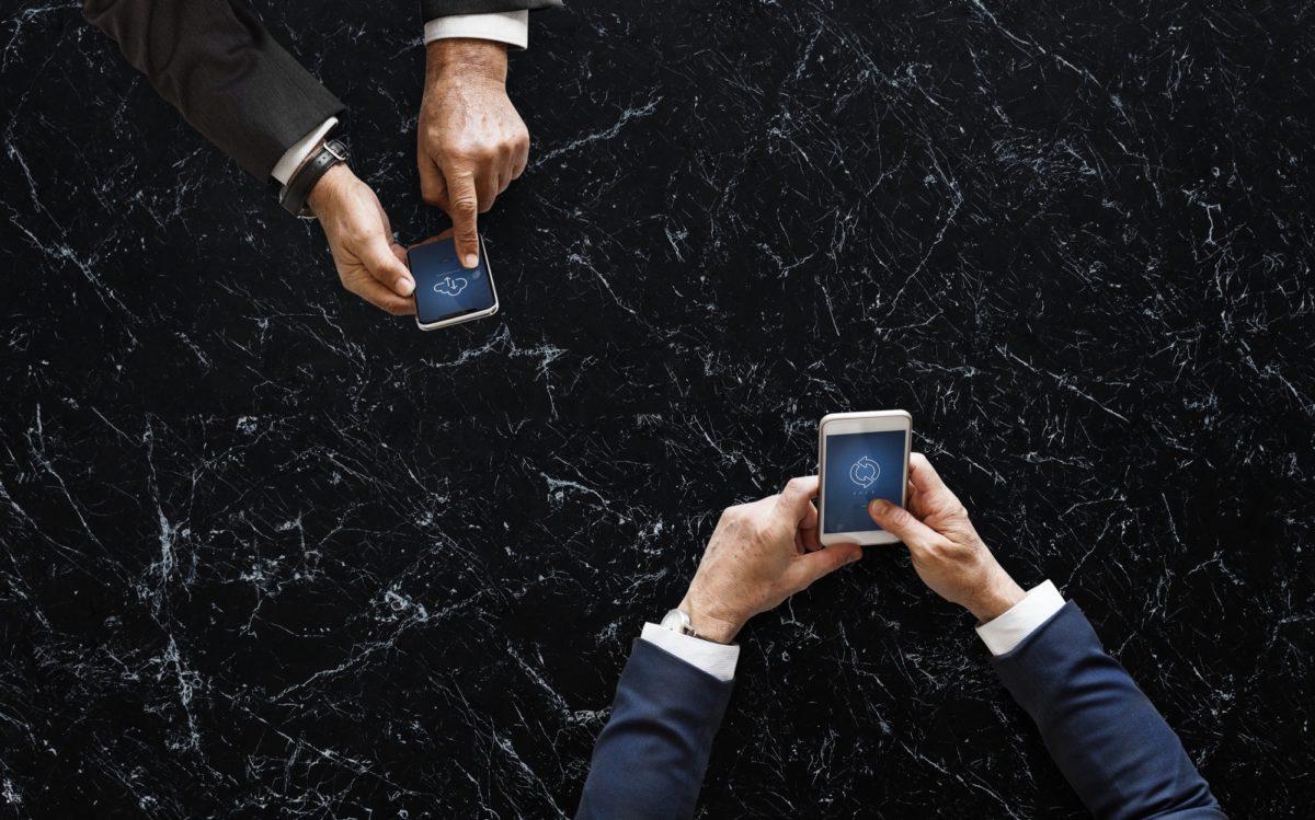 Foto: Arme und Hände von zwei Anzugsträgern, die jeweils ein Smartphone in den Händen halten