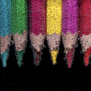 Foto: Reihe von Buntstiften, die unter Wasser liegen und von Luftbläschen umgeben sind
