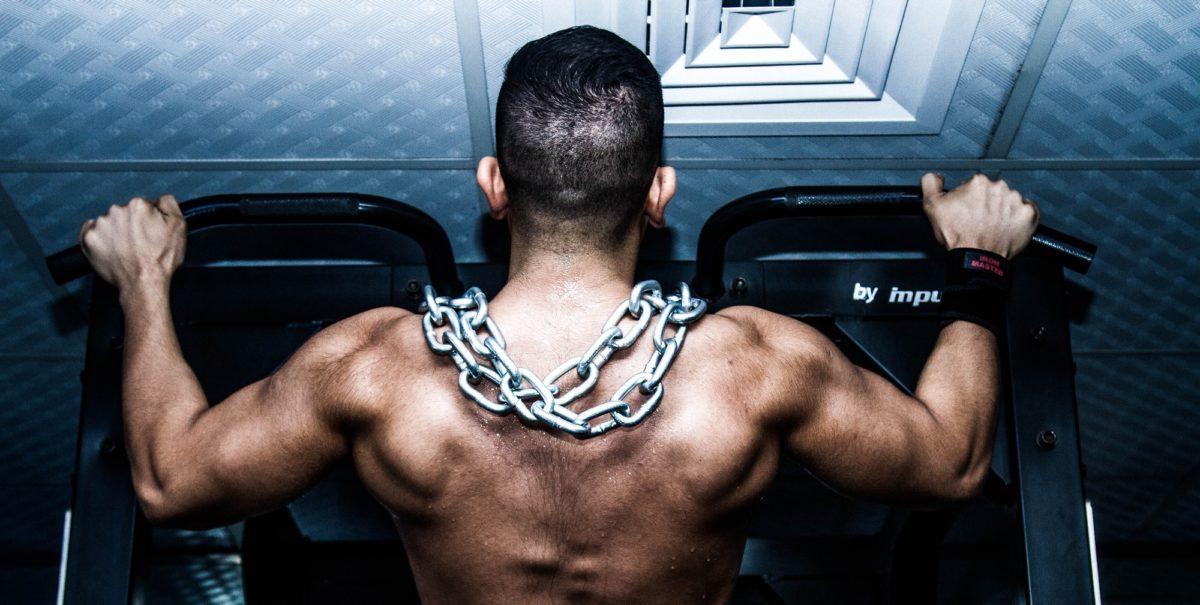 Foto: Mann mit nacktem Oberkörper und einer Kette um den Hals, der Krafttraining an einer Maschine betreibt (von hinten fotografiert)