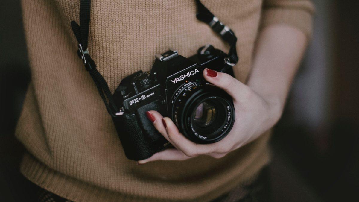 Foto: Fotokamera, die von einer weiblichen Hand gehalten wird