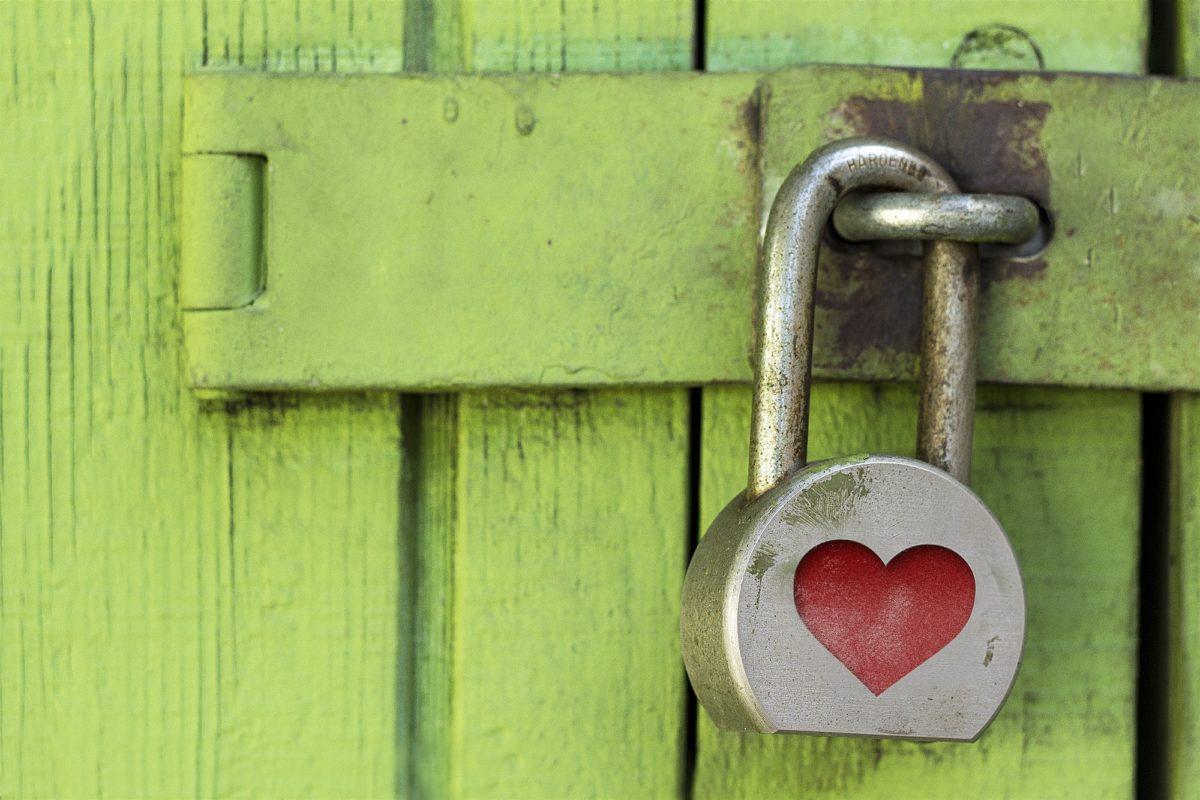 Foto: Vorhängeschloss mit einem roten Herz, das eine grüne Holztüre abschliesst