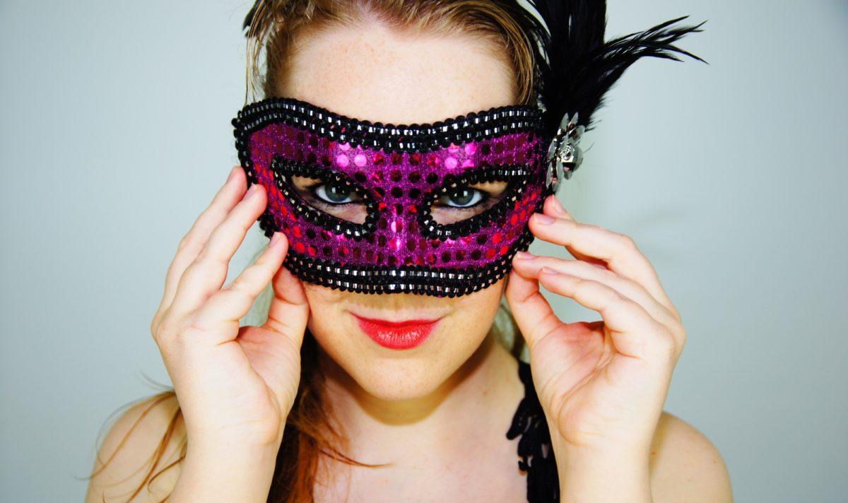 Foto: Frau, die sich eine Maske vor das Gesicht hält