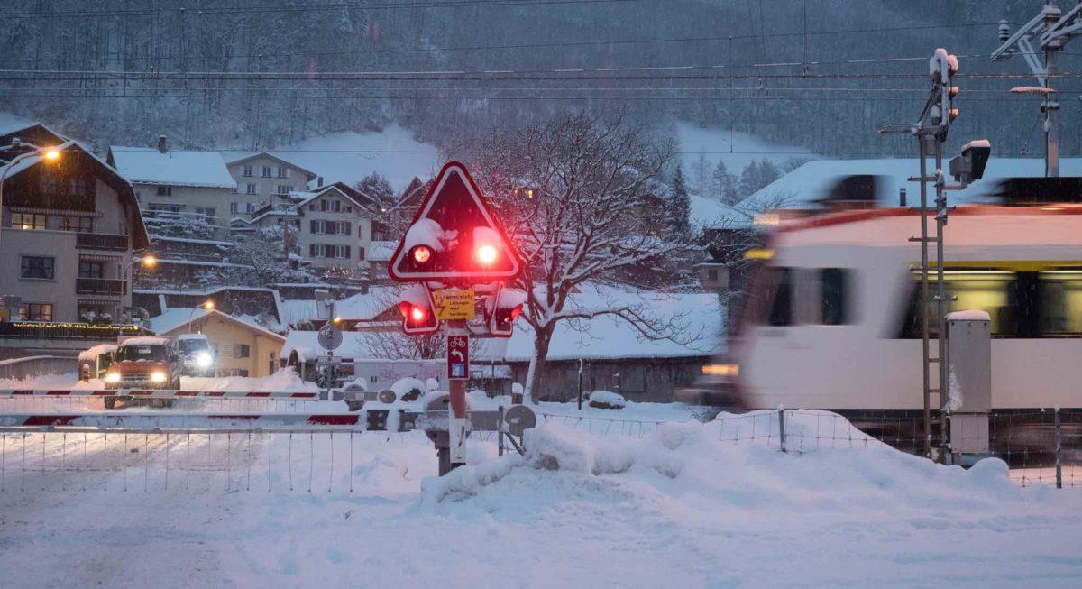 Foto: Geschlossener Bahnübergang mit blinkenden Warnlichtern