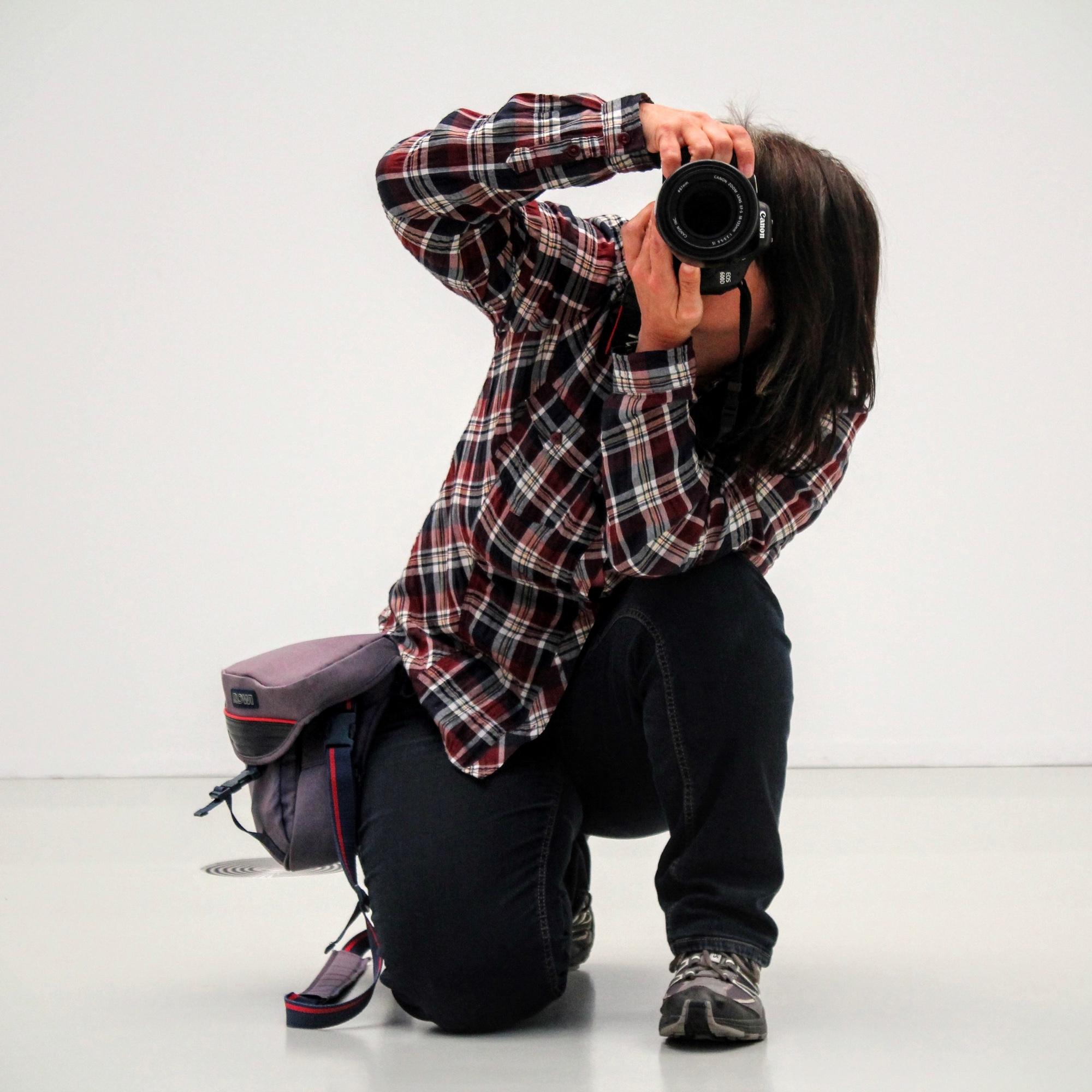 Foto: Fotografin, die kniet und eine Kamera for dem Gesicht hält