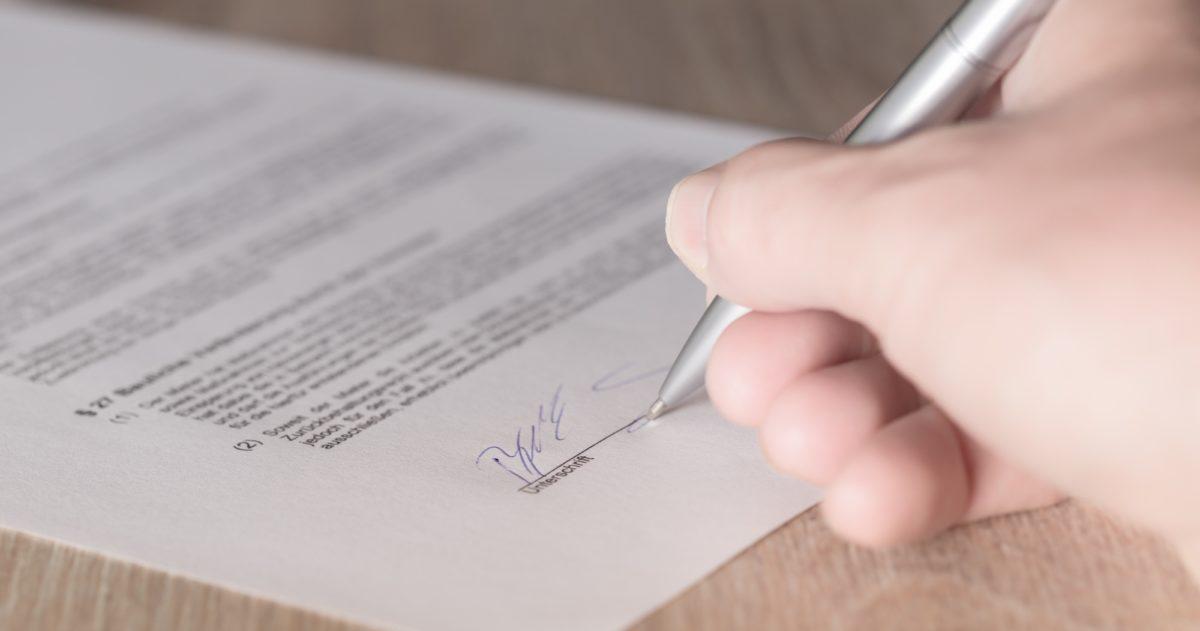 Foto: Handschriftliche Unterzeichnung eines Vertrages auf Papier