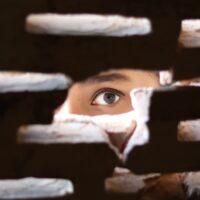 Foto: Person, die mit ihrem Auge durch ein Loch blickt