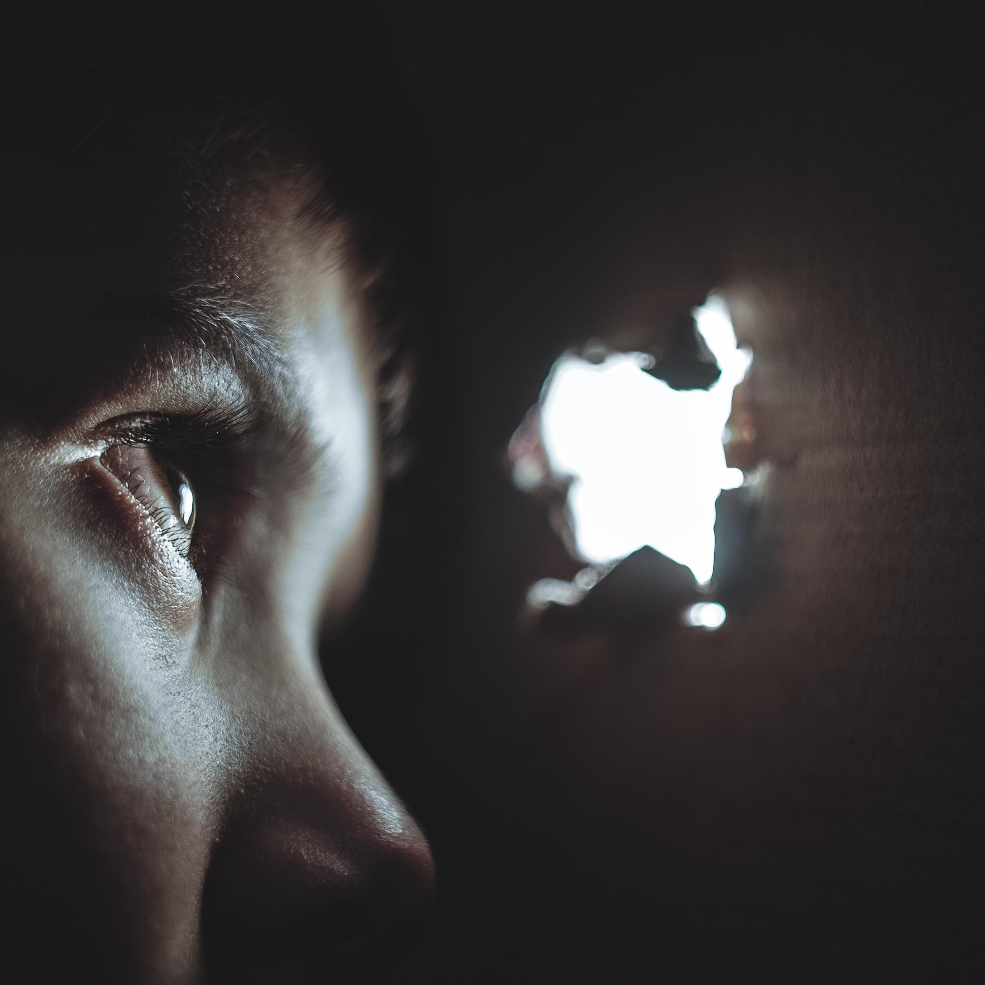 Foto: Kleiner Junge, der aus einem dunklen Versteck durch Loch nach draussen blickt