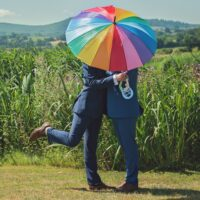 Foto: Gleichgeschlechtliches Paar hinter Regenbogen-Schirm