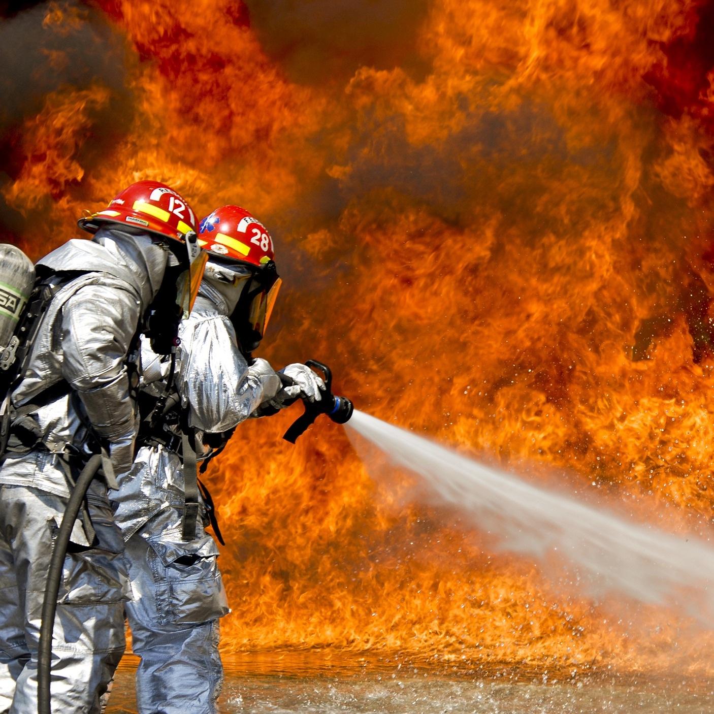 Foto: Feuerwehrleute, die einen Brand löschen